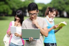 Estudiantes universitarios felices que usan el ordenador Foto de archivo libre de regalías