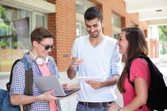 Estudiantes universitarios felices que usan el ordenador Imagen de archivo