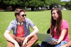 Estudiantes universitarios felices que usan el ordenador Fotos de archivo libres de regalías