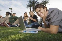 Estudiantes universitarios jovenes en césped del campus Imagen de archivo