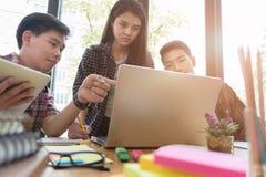 estudiantes universitarios jovenes que estudian con el ordenador y la tableta en c Fotografía de archivo libre de regalías