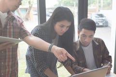 estudiantes universitarios jovenes que estudian con el ordenador y la tableta en c Fotos de archivo libres de regalías