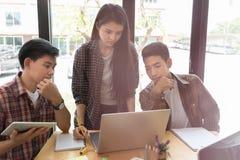 estudiantes universitarios jovenes que estudian con el ordenador y la tableta en c Imagen de archivo