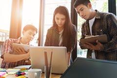 estudiantes universitarios jovenes que estudian con el ordenador y la tableta en c Imagenes de archivo