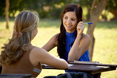 Estudiantes universitarios jovenes que hablan y que estudian para el examen de la universidad Imagen de archivo