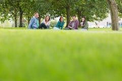 Estudiantes universitarios jovenes que se sientan en hierba en parque Fotos de archivo