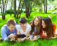 Estudiantes universitarios jovenes que usan la tableta Imágenes de archivo libres de regalías