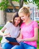 Estudiantes universitarios jovenes que usan la tableta Imagenes de archivo