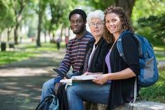 Estudiantes universitarios multiétnicos que se sientan en campus Imagen de archivo