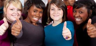 Estudiantes universitarios multirraciales con los pulgares para arriba Imagen de archivo libre de regalías