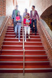 Estudiantes universitarios que caminan abajo de las escaleras en universidad Imagenes de archivo
