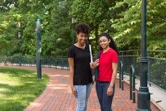 2 estudiantes universitarios que caminan en campus Imágenes de archivo libres de regalías
