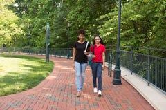 2 estudiantes universitarios que caminan en campus Foto de archivo libre de regalías