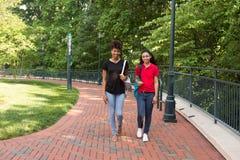 2 estudiantes universitarios que caminan en campus Imagenes de archivo