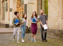 Estudiantes universitarios que caminan en campus Fotografía de archivo