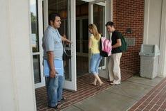 Estudiantes universitarios que entran en la biblioteca. Fotografía de archivo libre de regalías