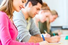 Estudiantes universitarios que escriben la prueba o el examen Fotografía de archivo libre de regalías