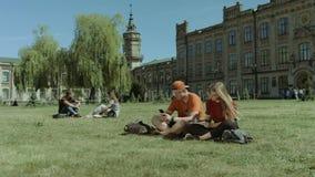 Estudiantes universitarios que estudian en césped del campus almacen de metraje de vídeo
