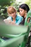 Estudiantes universitarios que estudian en el libro de textos en parque Fotos de archivo