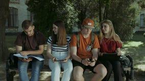 Estudiantes universitarios que estudian junto en el banco almacen de video