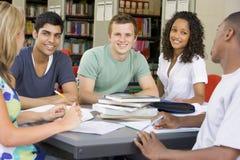 Estudiantes universitarios que estudian junto en una biblioteca imagenes de archivo