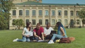 Estudiantes universitarios que estudian la sentada en c?sped verde almacen de metraje de vídeo