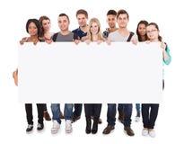 Estudiantes universitarios que exhiben la cartelera en blanco Fotografía de archivo