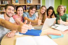 Estudiantes universitarios que gesticulan los pulgares para arriba en biblioteca Imagen de archivo