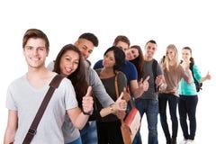 Estudiantes universitarios que gesticulan los pulgares para arriba en una línea foto de archivo libre de regalías