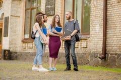 Estudiantes universitarios que hablan alegre en campus Foto de archivo