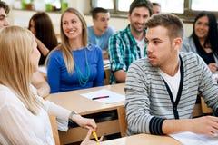 Estudiantes universitarios que hablan durante clase Imágenes de archivo libres de regalías