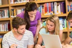 Estudiantes universitarios que hacen la preparación en biblioteca Imagenes de archivo