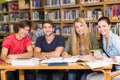 Estudiantes universitarios que hacen la preparación en biblioteca Imágenes de archivo libres de regalías