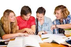 Estudiantes universitarios que hacen la preparación en biblioteca Imagen de archivo