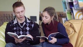 Estudiantes universitarios que leen las revistas en biblioteca almacen de metraje de vídeo
