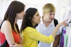 Estudiantes universitarios que miran un tablón de anuncios Imagen de archivo libre de regalías
