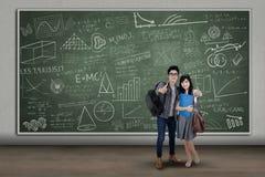 Estudiantes universitarios que muestran los pulgares-para arriba Imagen de archivo