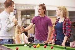 Estudiantes universitarios que relajan y que juegan al billar junto Fotos de archivo libres de regalías