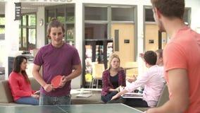 Estudiantes universitarios que relajan y que juegan a tenis de mesa almacen de metraje de vídeo