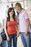 Estudiantes universitarios que se colocan en pasillo de la universidad Imágenes de archivo libres de regalías