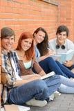 Estudiantes universitarios que se sientan afuera por la pared de ladrillo Imágenes de archivo libres de regalías