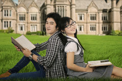 Estudiantes universitarios que se sientan en el parque de la universidad Imagenes de archivo