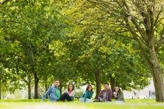 Estudiantes universitarios que se sientan en hierba en parque Foto de archivo libre de regalías