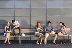 Estudiantes universitarios que se sientan en la pared moderna del banco Fotos de archivo libres de regalías