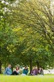 Estudiantes universitarios que se sientan en parque Foto de archivo libre de regalías