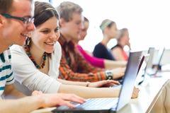 Estudiantes universitarios que se sientan en una sala de clase Imagenes de archivo