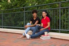 2 estudiantes universitarios que se sientan junto en campus Imagen de archivo