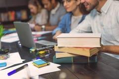 Estudiantes universitarios que se sientan junto y que estudian Imagen de archivo libre de regalías