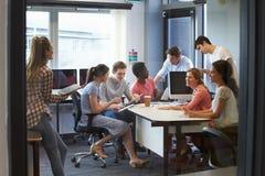 Estudiantes universitarios que tienen reunión informal con los profesores particulares fotos de archivo