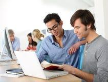 Estudiantes universitarios que trabajan con el libro y el ordenador portátil Foto de archivo libre de regalías
